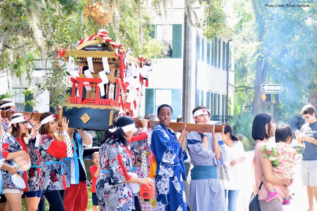 College students participate in the Japanese tradition of parading a Shinto shrine