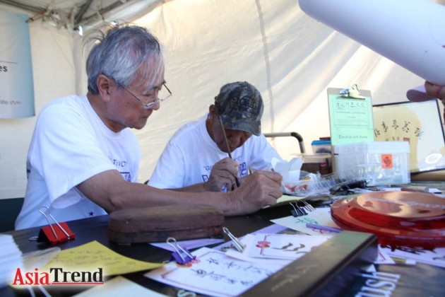 Roy Wang and Peter Lau from Youth Enrichment and Senior Services demonstrate the Art of Chinese Calligraphy to raise fund for a senior service center